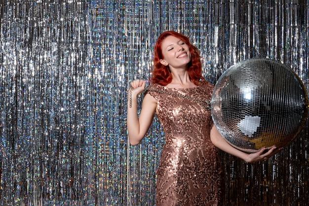 明るいカーテンカーテンでディスコボールを保持しているパーティーで新年を祝う若い女性