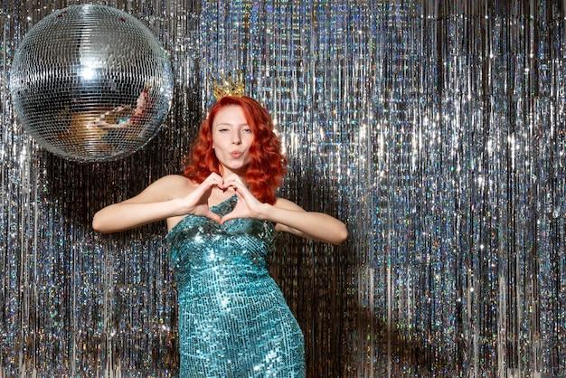 明るいカーテンカーテンの上の王冠とパーティーで新年を祝う若い女性