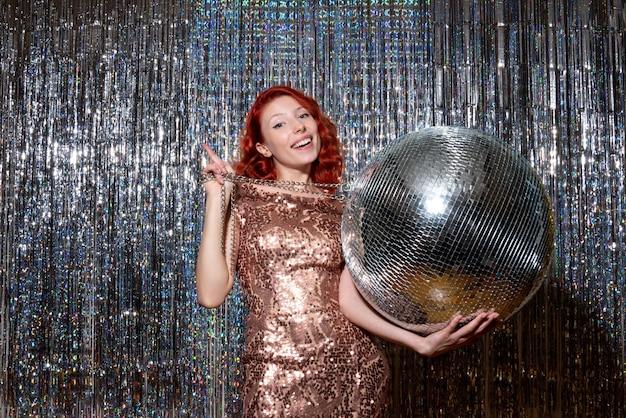 Giovane donna che celebra il nuovo anno in festa tenendo palla da discoteca su tende luminose tende
