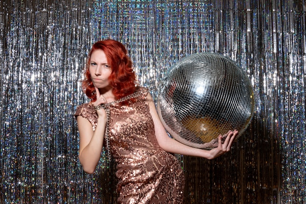 Young woman celebrating new year in party holding disco ball on bright curtains curtains