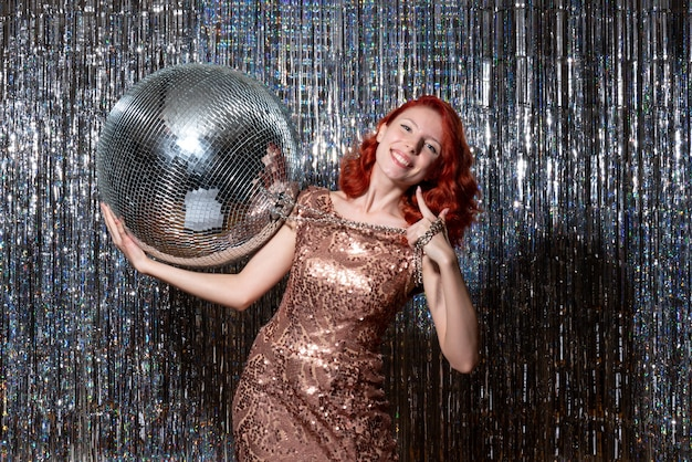 Young woman celebrating new year in party holding disco ball on bright curtains