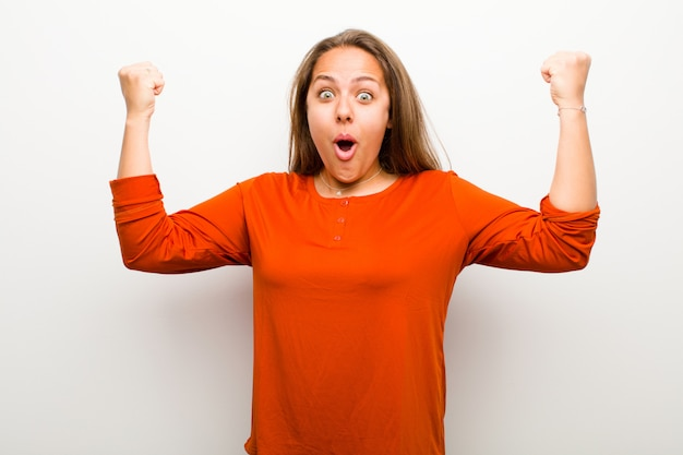 Young woman celebrating an unbelievable success like a winner, looking excited and happy saying take that! over white wall