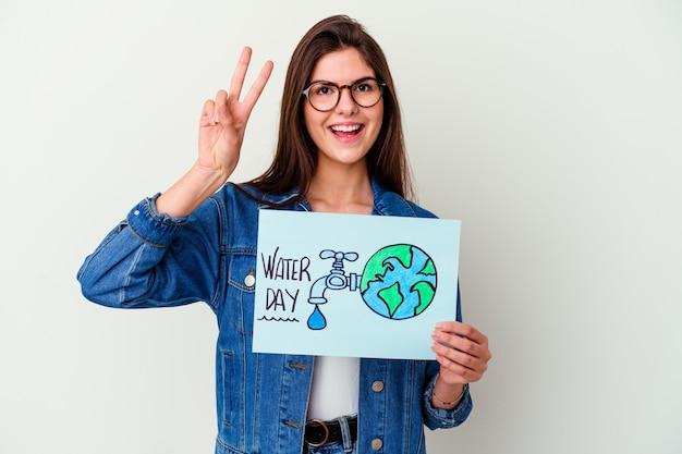 ピンクの壁に隔離された世界水の日を祝う若い女性が指で2番目を示しています
