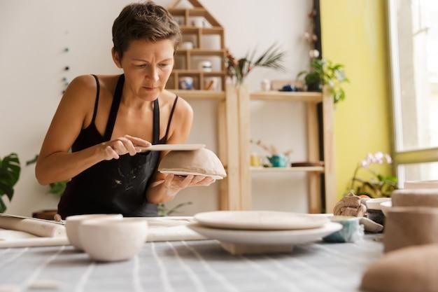 Молодая женщина керамической и гончарной посуды в мастерской