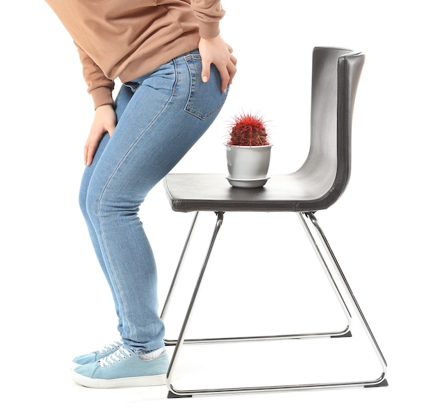 Young woman and chair with cactus on white surface. hemorrhoids concept