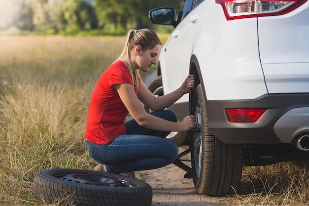 Молодая женщина меняет спущенную шину в поле