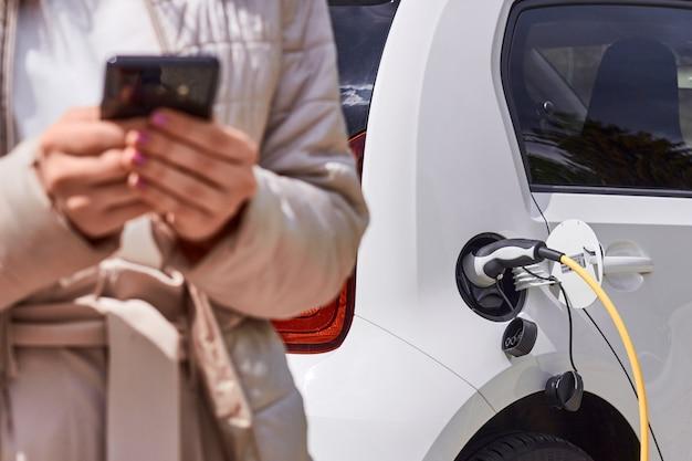 Молодая женщина заряжает электромобиль на общественной зарядной станции и платит с помощью мобильного телефона. инновационный экологичный автомобиль.