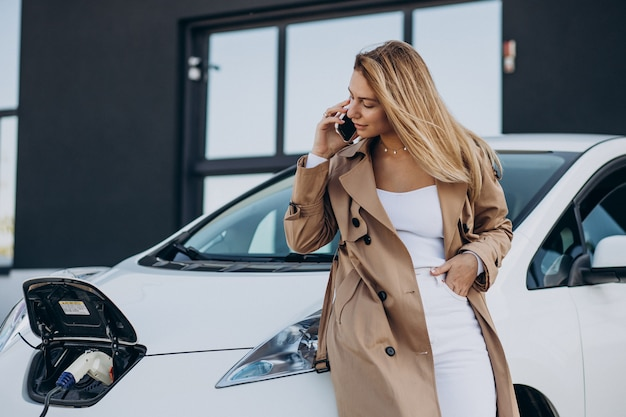 Young woman charging her electric car with charging pistol