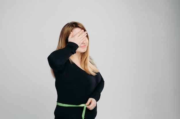 Young woman check her stomach fat with line tape, gesturing facepalm