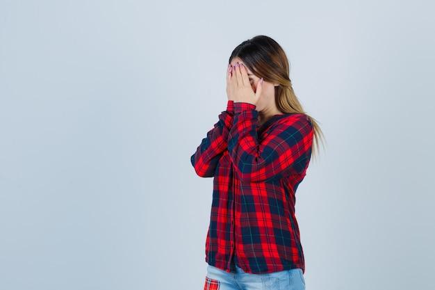 Giovane donna in camicia a quadri che copre il viso con le mani e sembra depressa, vista frontale.