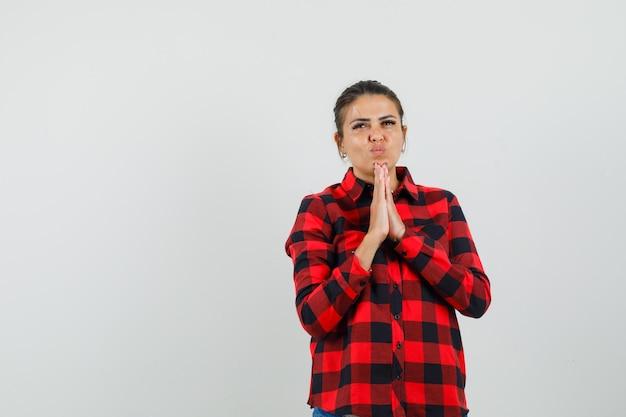 Giovane donna in camicia a quadri tenendo le mani nel gesto di preghiera e guardando speranzoso, vista frontale.