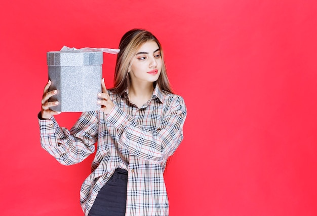 Giovane donna in camicia a quadri che tiene in mano una confezione regalo d'argento e si sente felice