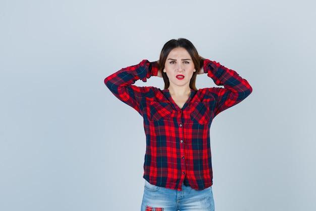 Giovane donna in camicia a quadri, jeans che tiene le mani dietro la testa e sembra confusa, vista frontale.