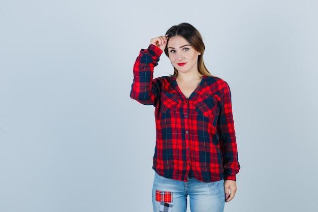 Giovane donna in camicia a quadri, jeans guardando davanti con la mano sulla testa e guardando vergogna, vista frontale.