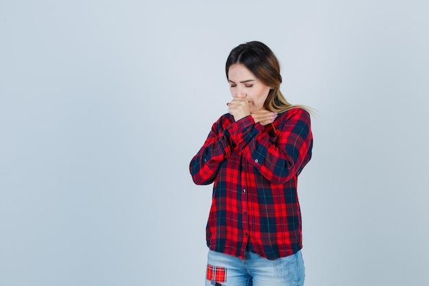 Giovane donna in camicia a quadri, jeans che soffre di tosse e sembra malata, vista frontale.