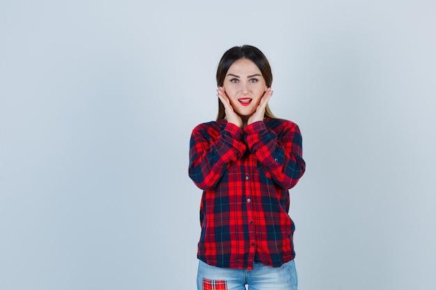 Giovane donna in camicia a quadri che tiene le mani sulle guance e si vergogna, vista frontale.