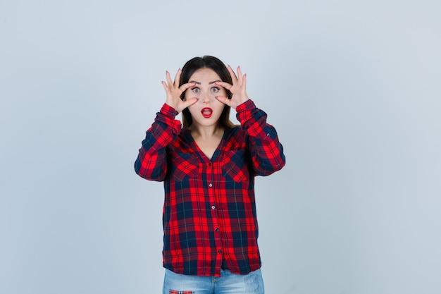 Giovane donna in camicia a quadri guardando attraverso le dita e guardando domandata, vista frontale.