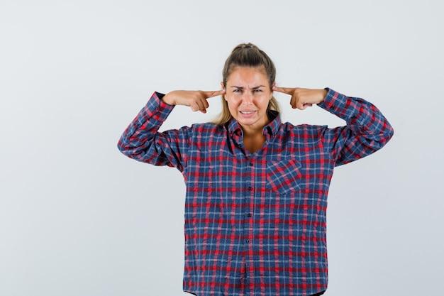 Giovane donna in camicia a quadri tappando le orecchie con le ali indice e guardando tormentata