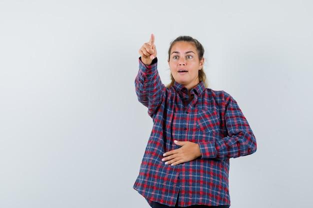 Giovane donna in camicia a quadri che punta lontano e che sembra carina