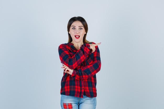 Giovane donna in camicia a quadri che punta a destra e sembra stupita, vista frontale.