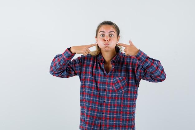 Giovane donna in camicia a quadri sbuffando guance mentre indicava e guardando divertito
