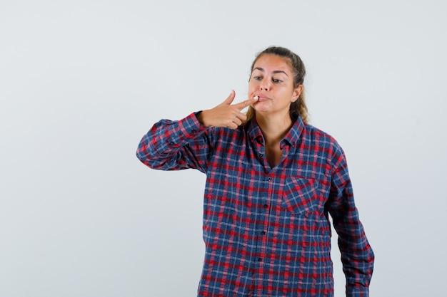 Giovane donna in camicia controllata che mette il dito indice sulla bocca e sembra seria