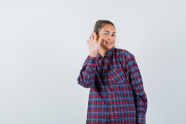 Giovane donna in camicia a quadri alzando la mano come saluto qualcuno e guardando amabile