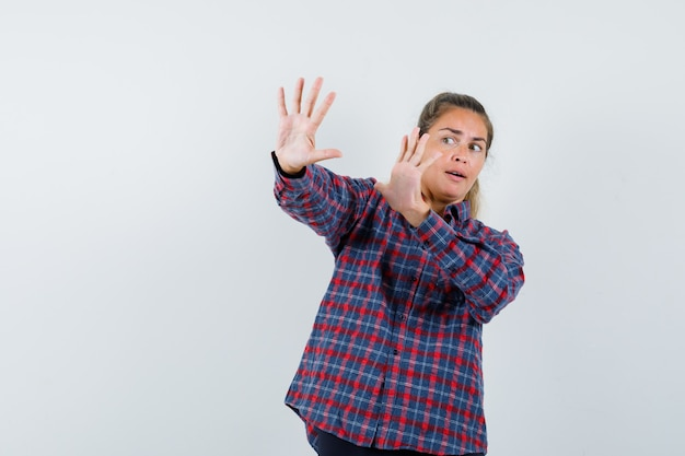 Young woman in checked shirt raising hands as trying to stop something and looking scared