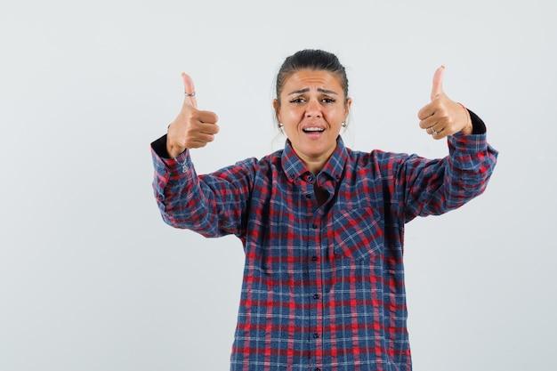 Giovane donna in camicia a quadri che mostra i pollici in su e che sembra felice, vista frontale.