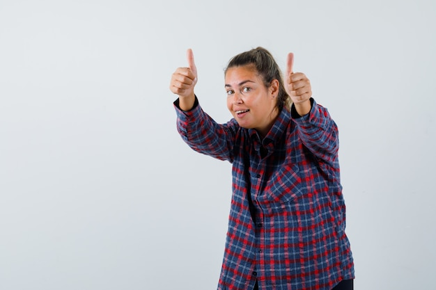 Young woman in checked shirt showing thumbs up with both hands and looking happy