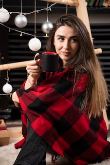Young woman in checkered plaid holding a hot cup.