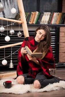 Giovane donna in plaid a scacchi seduta sul pavimento e leggendo un libro.