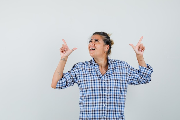 Young woman in checkered shirt pointing up and looking energetic.