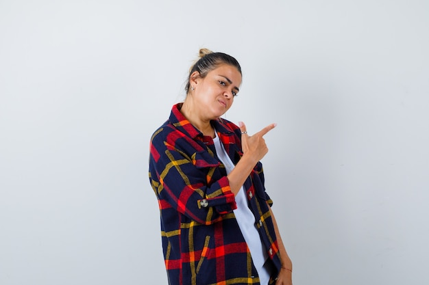 Young woman in checkered shirt pointing up, standing sideways and looking wistful .
