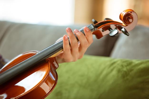 Молодая женщина проверяет скрипку дома.