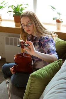 自宅でバイオリンをチェックする若い女性。