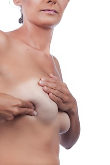 Young woman checking breast (auto self exam) for anomalies, nodes or weird lumps for breast cancer.