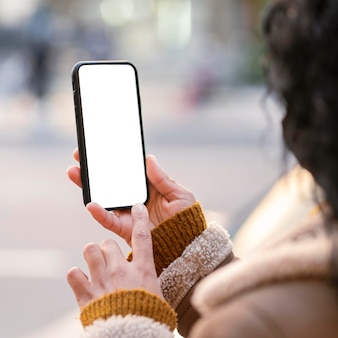 Young woman checking an empty screen smartphone