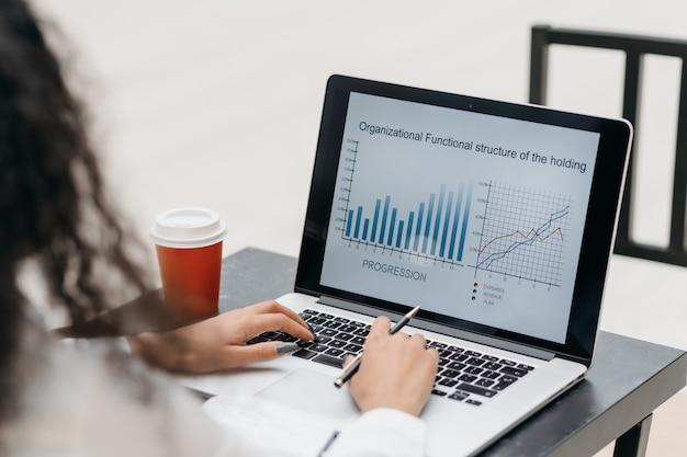 Молодая женщина проверяет финансовые данные, сидя за столом в кафе