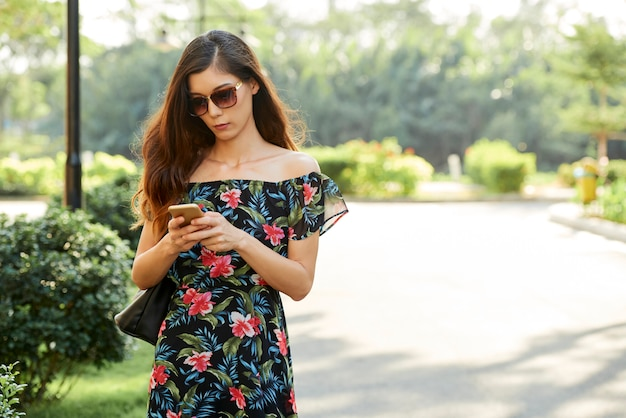若い女性は彼女の電話をチェック