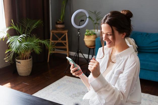 スマートフォンで彼女のvlogをチェックする若い女性