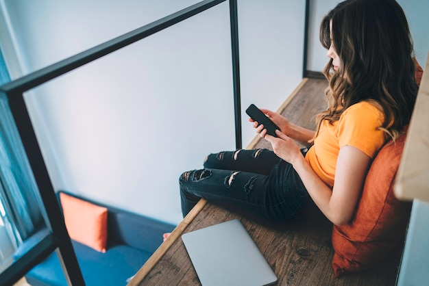 Молодая женщина проверяет сообщение на своем мобильном телефоне, сидя в своей двухуровневой комнате