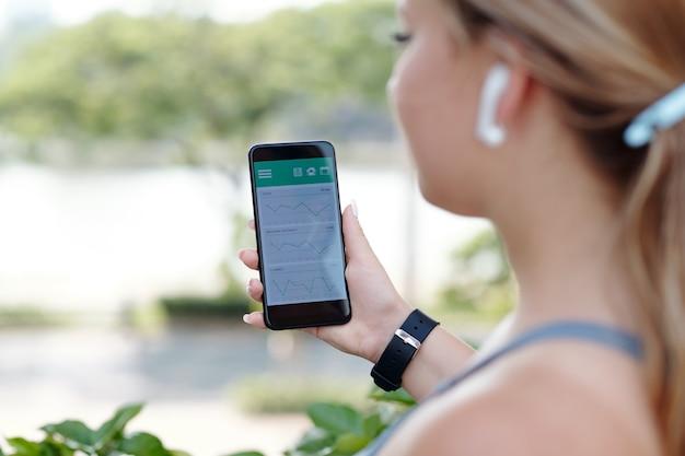 걷기 운동을 추적하고 속도, 거리 및 경로를 보여주는 모바일 애플리케이션을 확인하는 젊은 여성