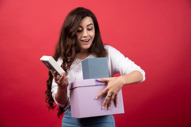 파란색 선물 상자를 체크 아웃하는 젊은 여자. 고품질 사진