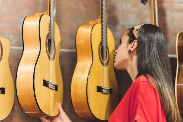 상점에서 구매하기 위해 기타를 확인하는 젊은 여성