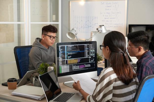 コンピュータ画面でプログラミングコードをチェックし、印刷されたドキュメントのコードと比較する若い女性