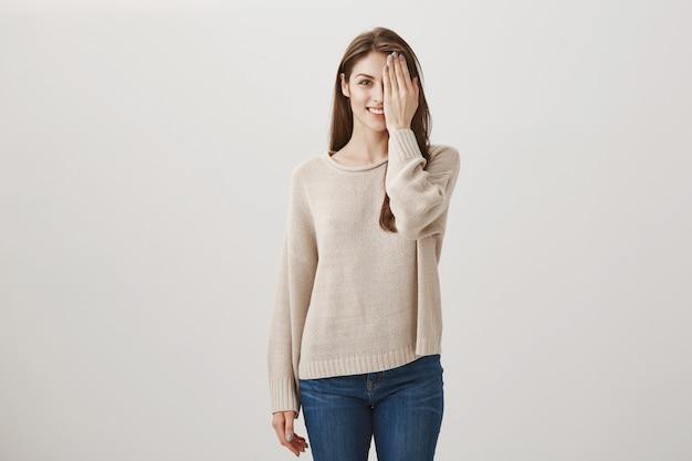 Молодая женщина, проверяя зрение, против половины лица и улыбается. до и после концепции