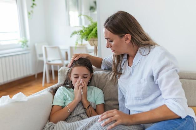 小さな病気の娘の手で温度をチェックする若い女性。病気の女の子の体温をチェックしている母親。手で額の熱をチェックしている女性と毛布の下のベッドに横たわっている病気の子供。