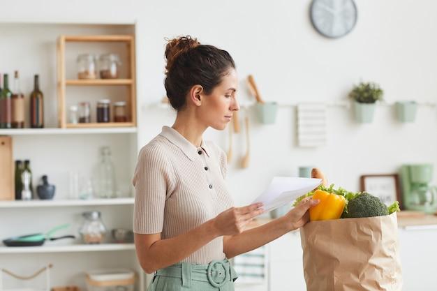 Молодая женщина проверяет продукты из списка после покупок, стоя на кухне