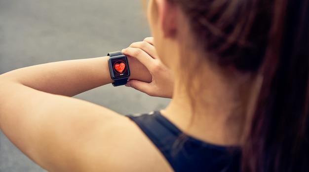 실행 후 심장 박동 및 성능을 측정하는 스포츠 시계를 확인하는 젊은 여자.